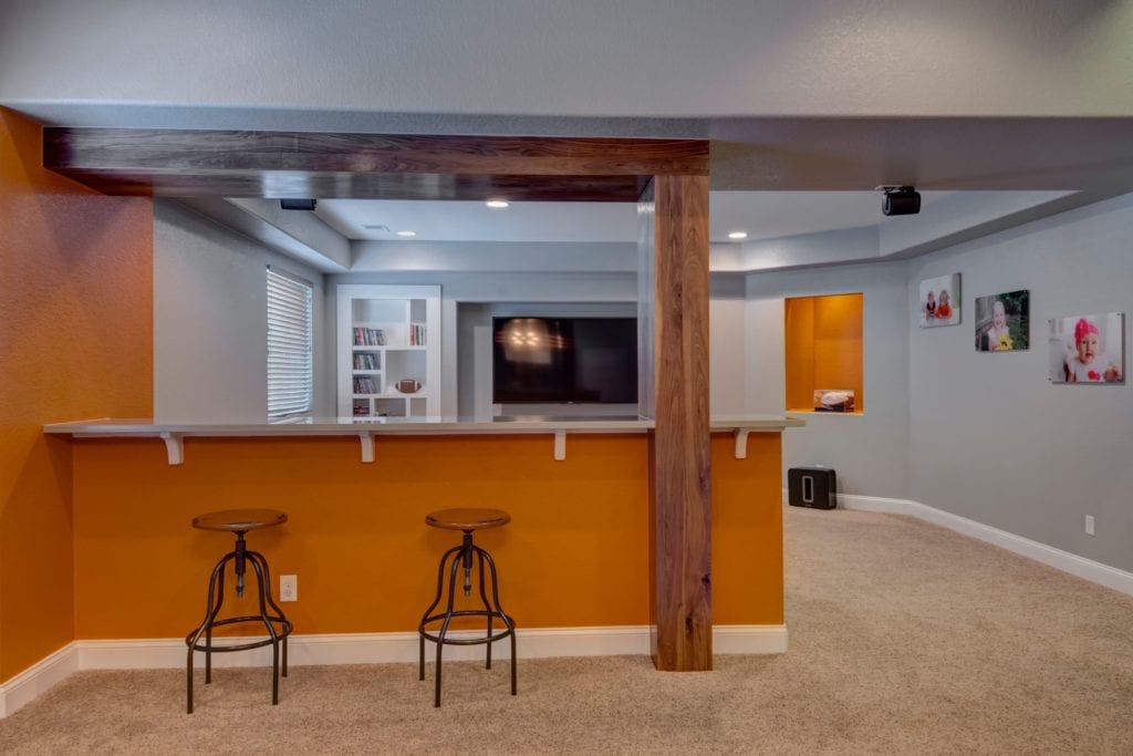 basement remodel with a wet bar and orange wall accents fbc remodel